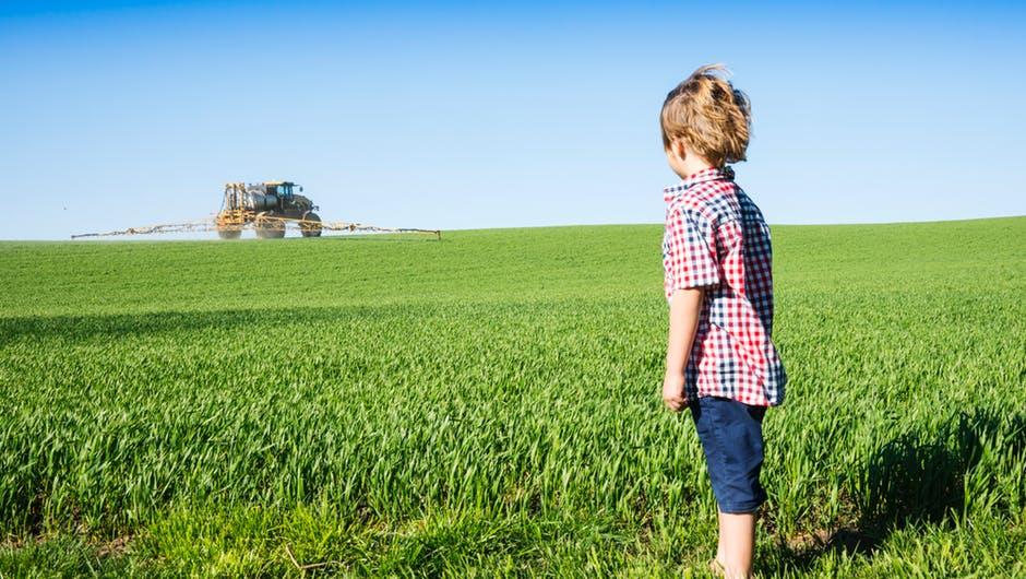 Pesticides un enfant regarde une machine d'épandage de pesticides